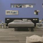 Aranżacja sypialni z jasnymi panelami podłogowymmi w szarościach