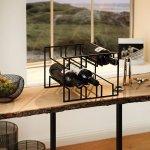 Metalowy stojak na wino na drewnianym stoliku