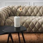 beżowa, pikowana sofa przy czarnym stoliku