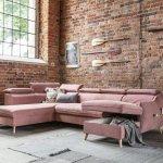 Różowa, rozkładana sofa na tle ceglanej ściany